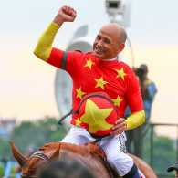 Mike Smith celebrates following his historic Triple Crown win