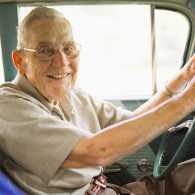 A senior man at the wheel of a car