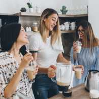 A group of friends having smoothies in a kitchen.