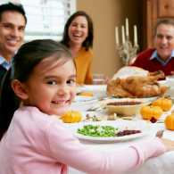 A smiling family surround a dining table filled with Thanksgiving favorites