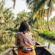 A woman on a tropical vacation sailing on a  river in a kayak.