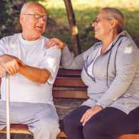 A caregiver engaged in conversation with her loved one on a bench outside.