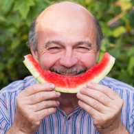 An older gentleman enjoying a slice of watermelon.