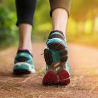 A woman walks for exercise on a jogging path