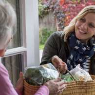 Woman giving senior woman a basket of food