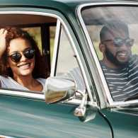 A smiling young couple smile from the front seat of their car as they depart on a road trip