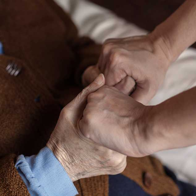 A caregiver clasps hands with the senior woman in her care