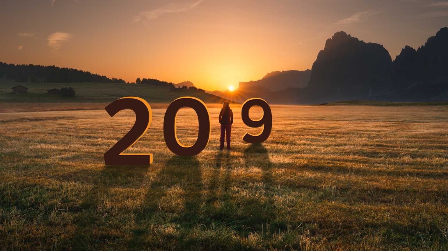 A woman in a field greets the new year at sunrise