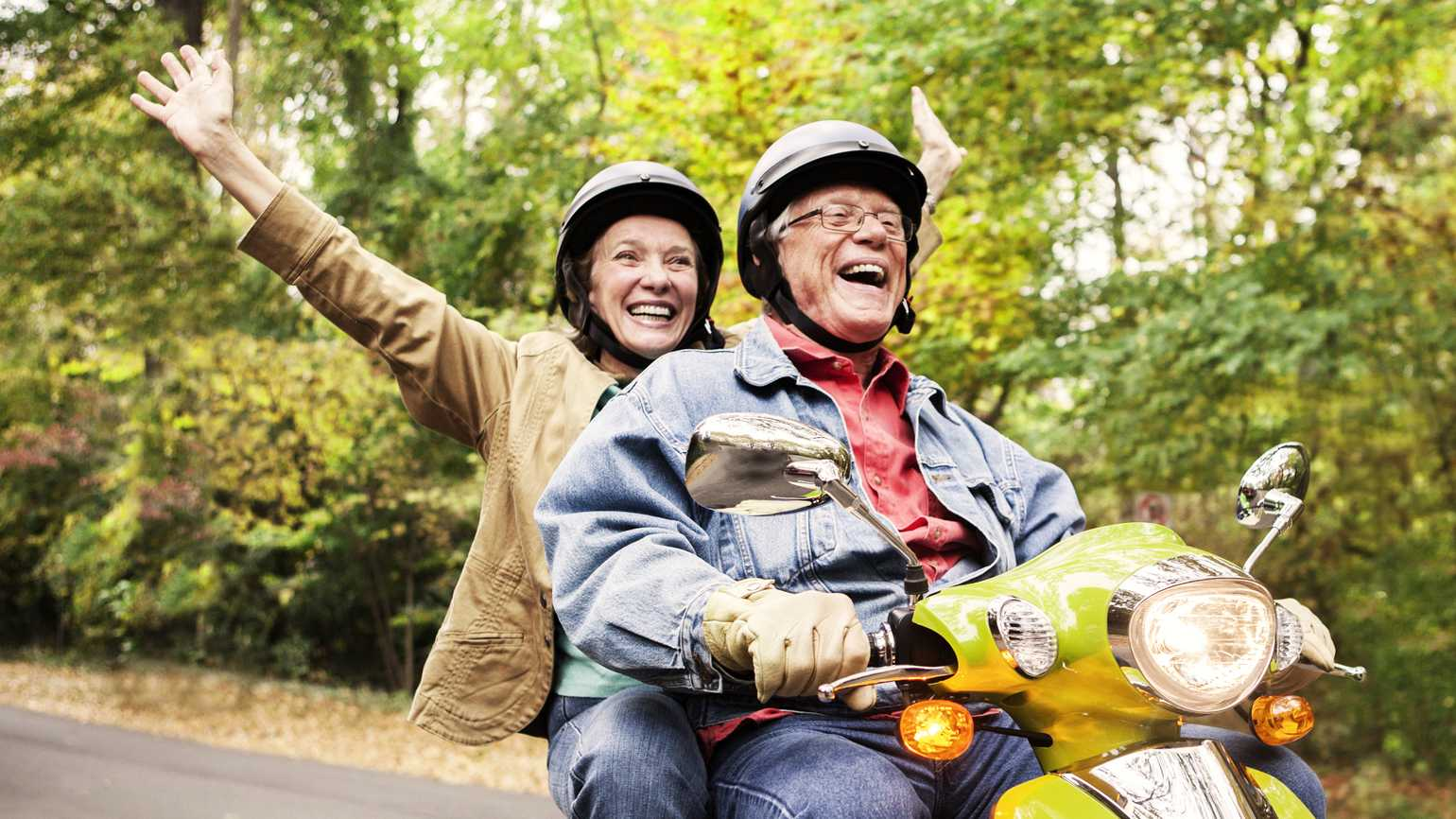 A retired couple having a blast on a motorcycle through the woods.
