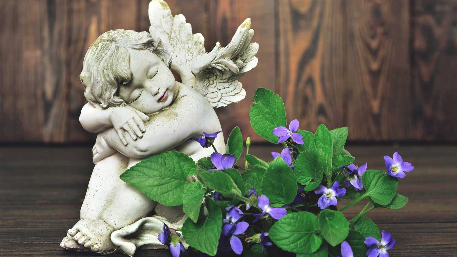 A angel cherub figurine with small, violet flowers.