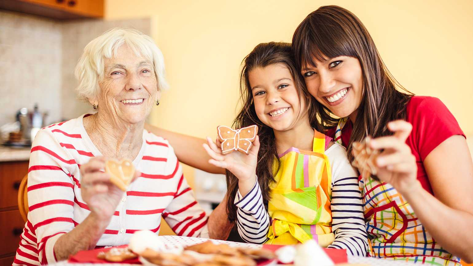 A senior woman, her daughter and granddaughter make holiday cookies