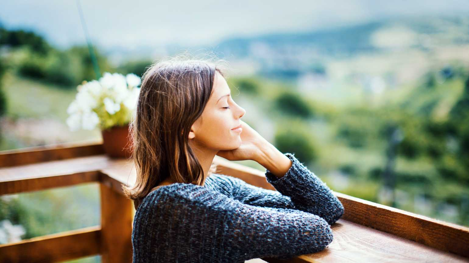 A woman with a calm mindset and closed eyes enjoying the outdoors.