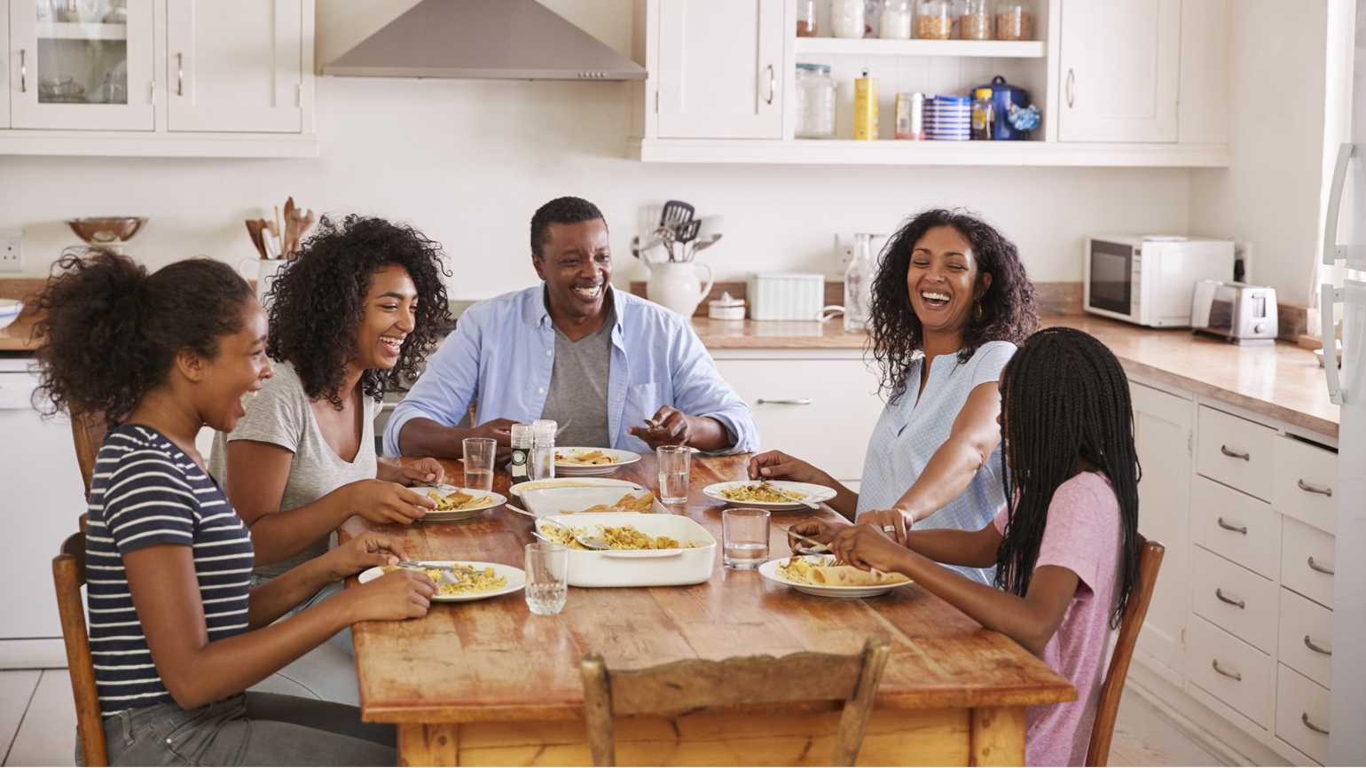 A diverse happy family having dinner.