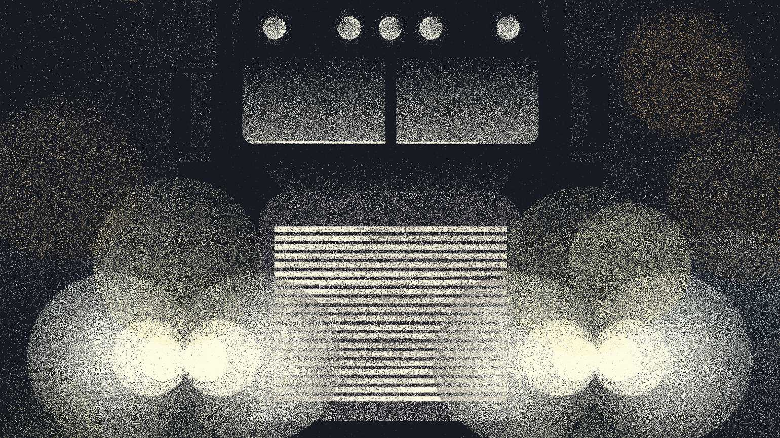 A large truck with gleaming headlights in on the road at night.
