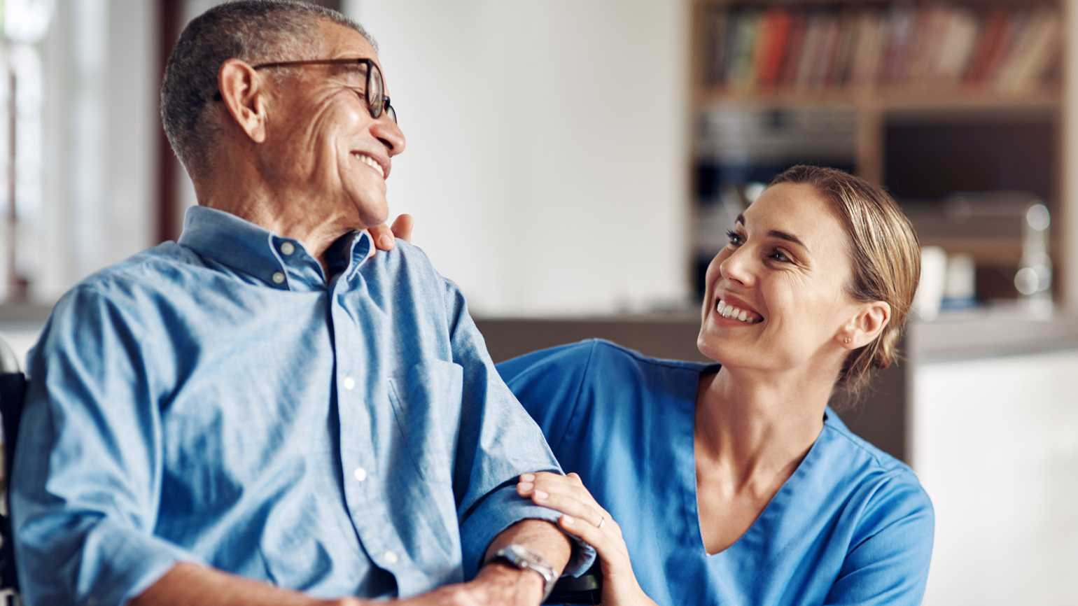 An in-home caregiver smiling at her client.