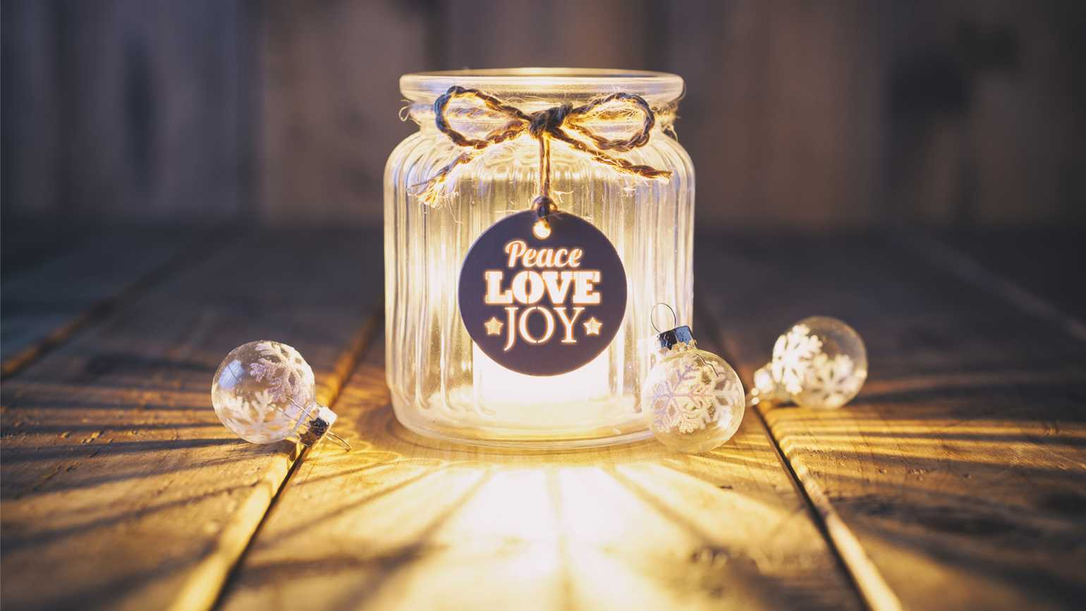 A jar that reads 'Peace Love Joy' with a lighted candle as well as snowflake ornaments.