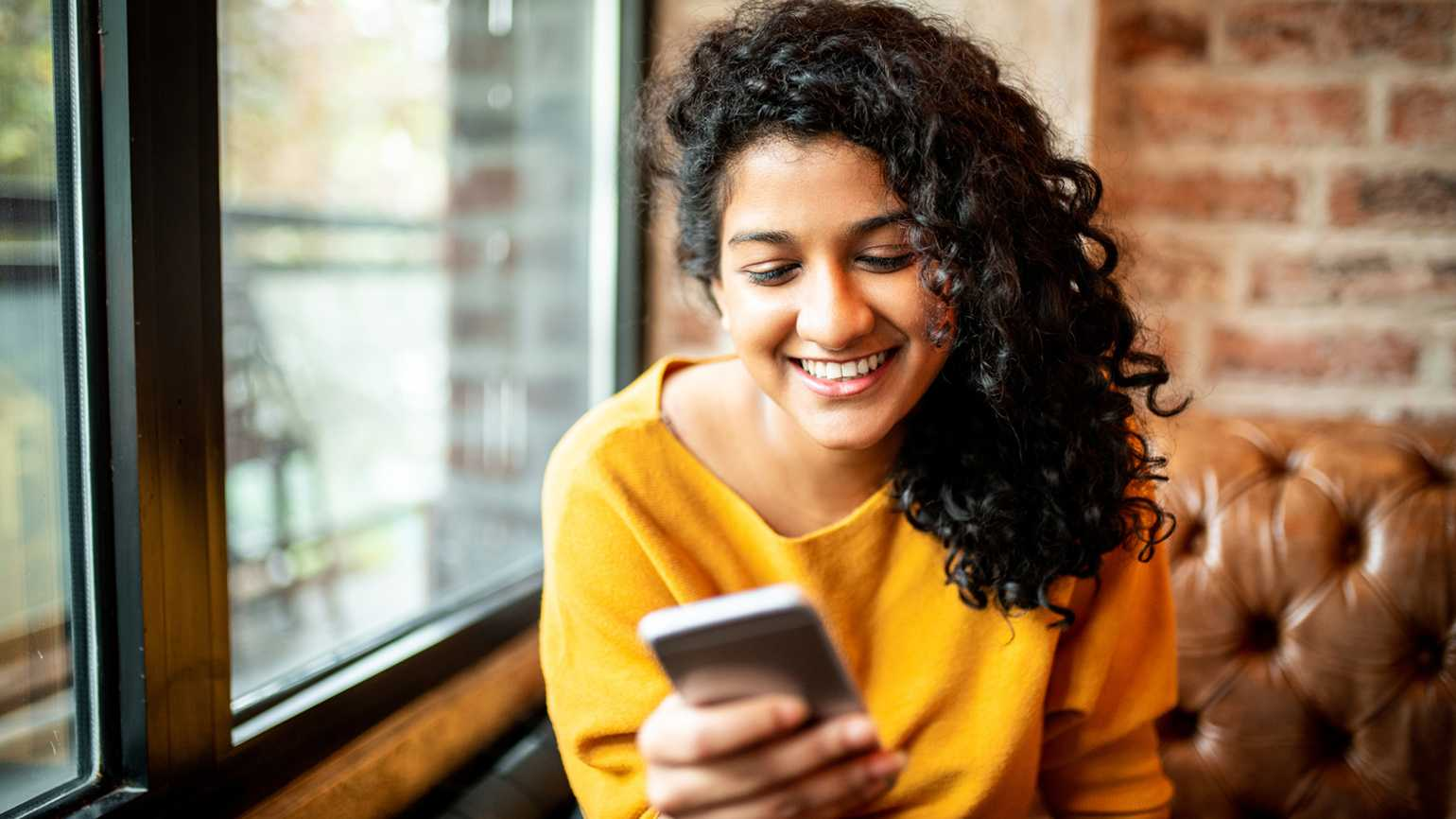 A woman using her phone happily.