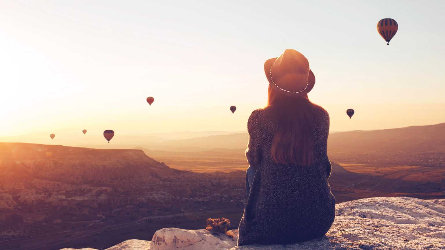 View from the back of a girl in a hat sits on a hill, looking at air balloons in Cappadocia in Turkey.