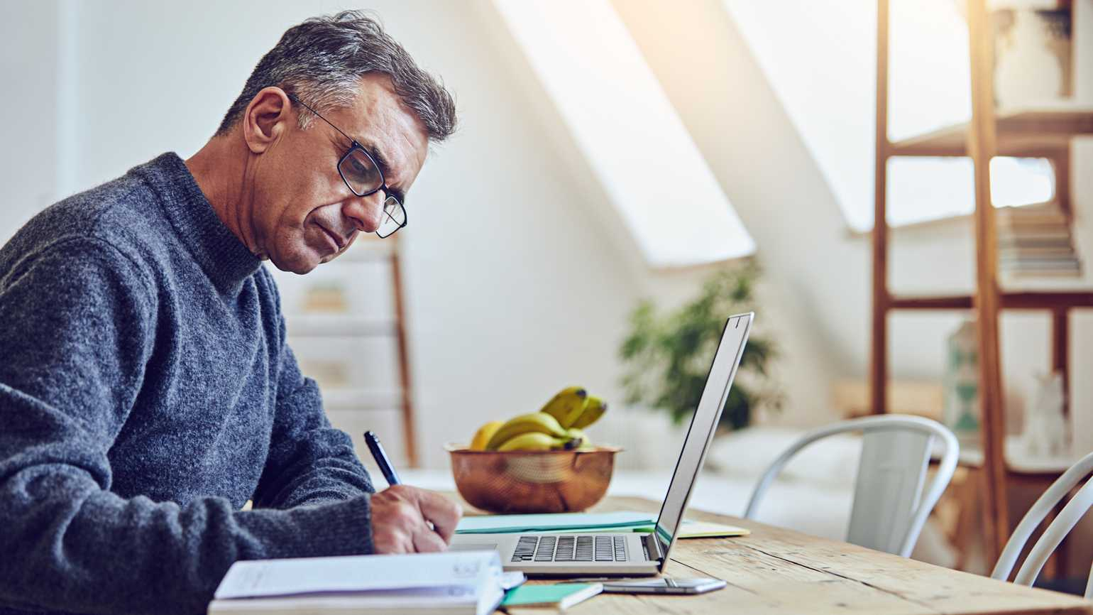 A male caregiver searching online and taking notes.