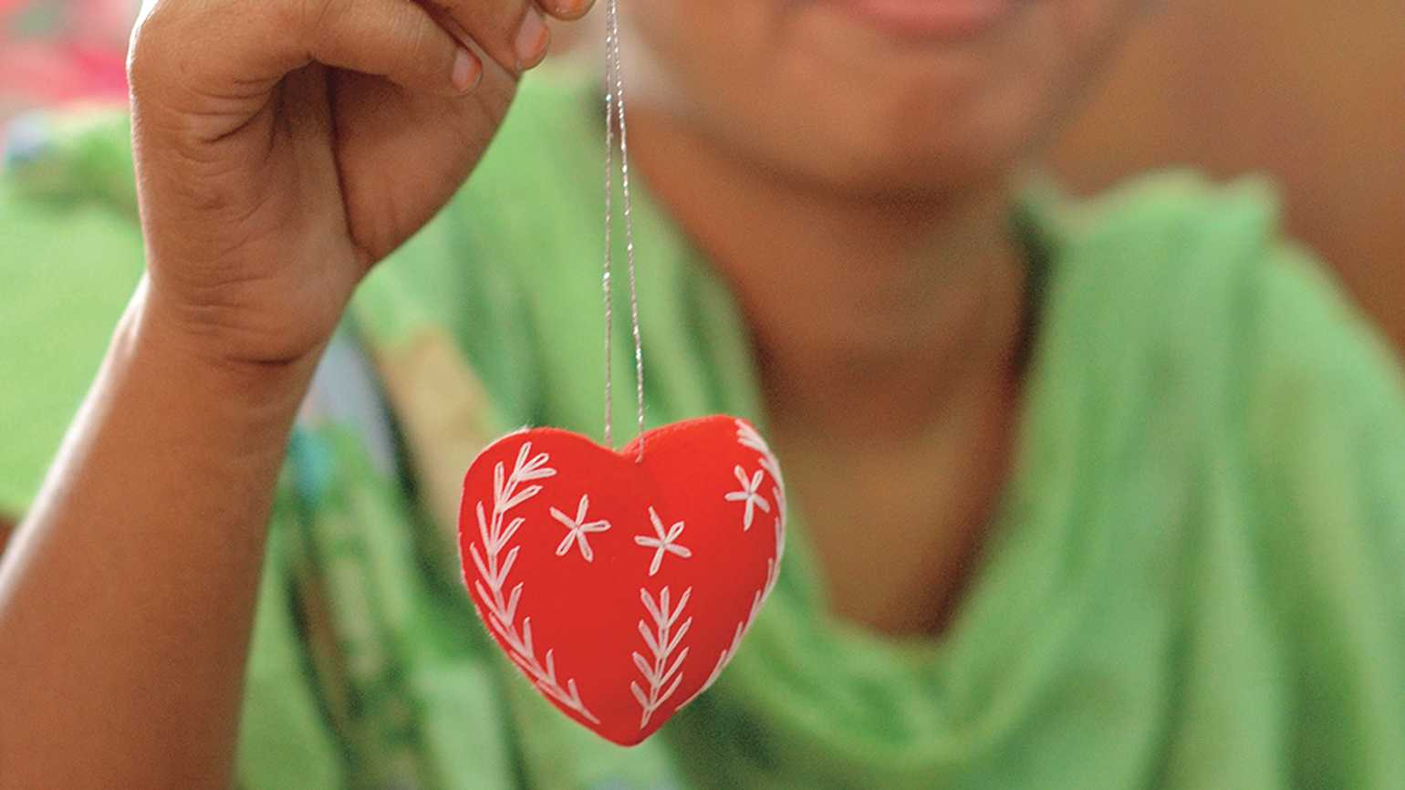 A young woman displays the red heart she has made