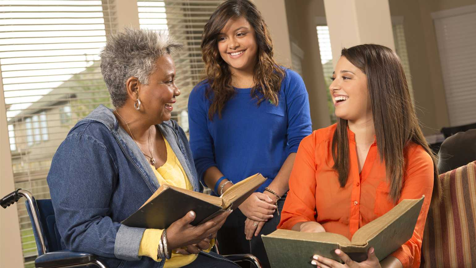 A young caregiver tells a story to a loved one in a nursing home.