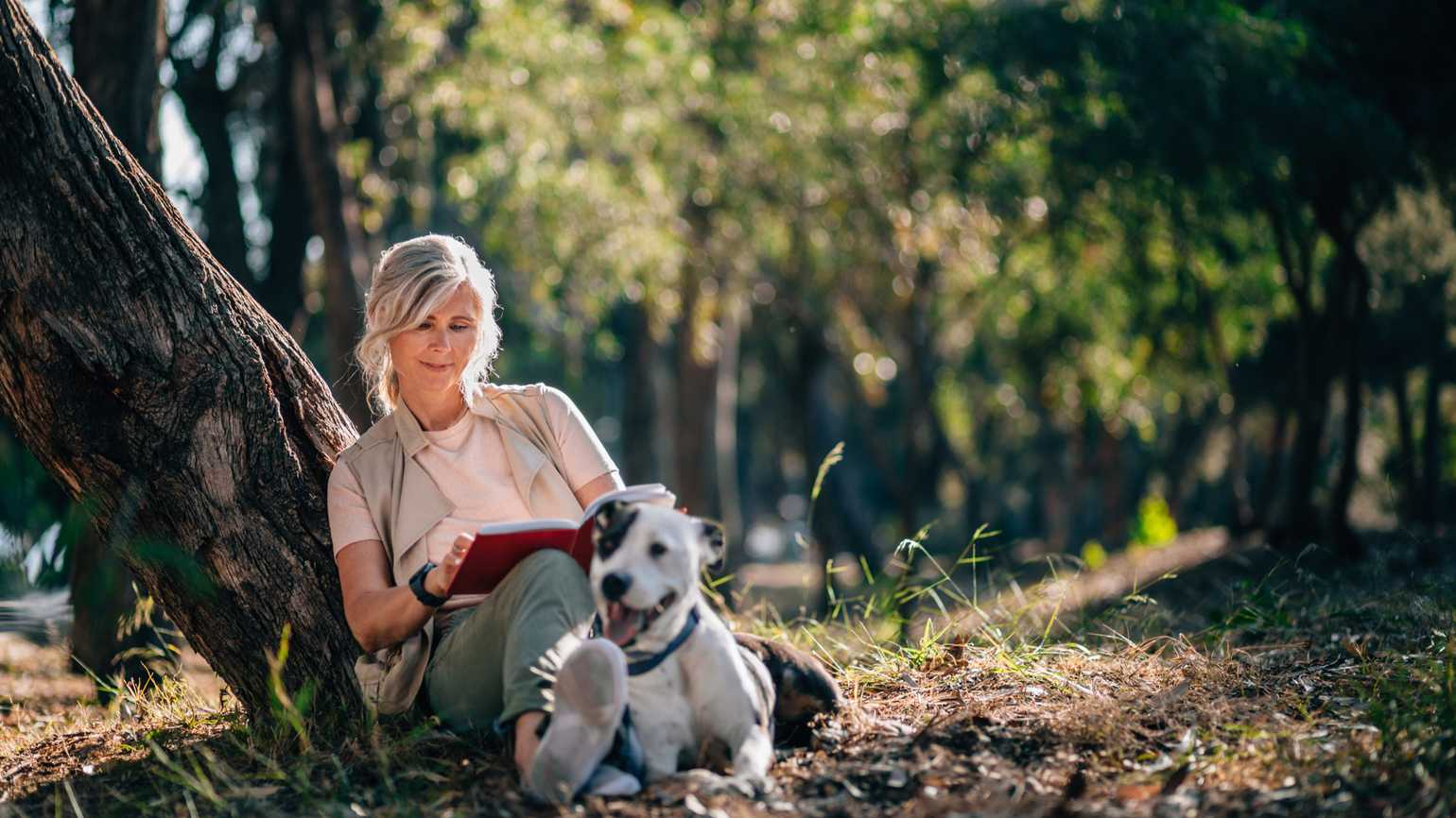 A woman reading outside with her dog.
