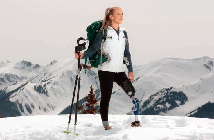 Kirstie Ennis stands atop a snow-covered mountain