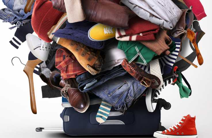 A suitcase piled with various clothes and belongings.