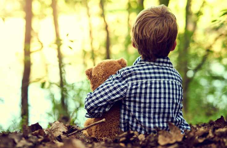 A young boy holding a teddy bear in a  forest.