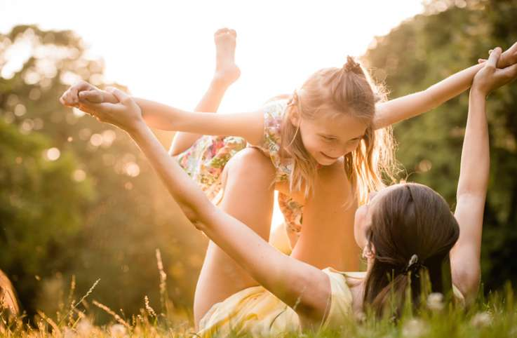 Mom lifts up her daughter as the sun glows in the background My Kids Taught Me How to Live