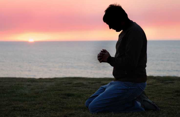 A man deep in prayer as the sun sets against the ocean.