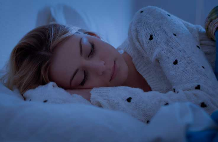 A young woman sleeping in bed during the night.