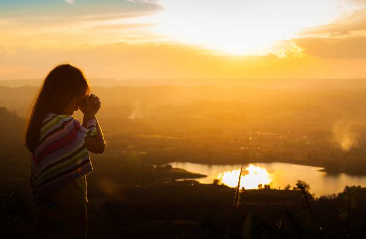 A young girl praying outdoors during the sunset.