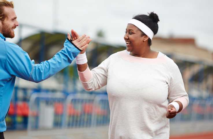 A young woman running on a track with the guidance of her personal trainer.