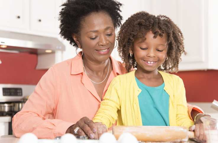 A grandmother baking with her granddaughter.