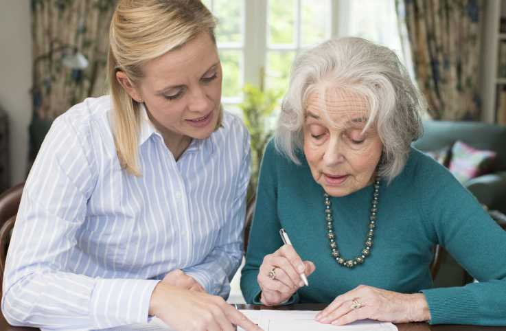 A caregiver helping her loved one with power of attorney paperwork.