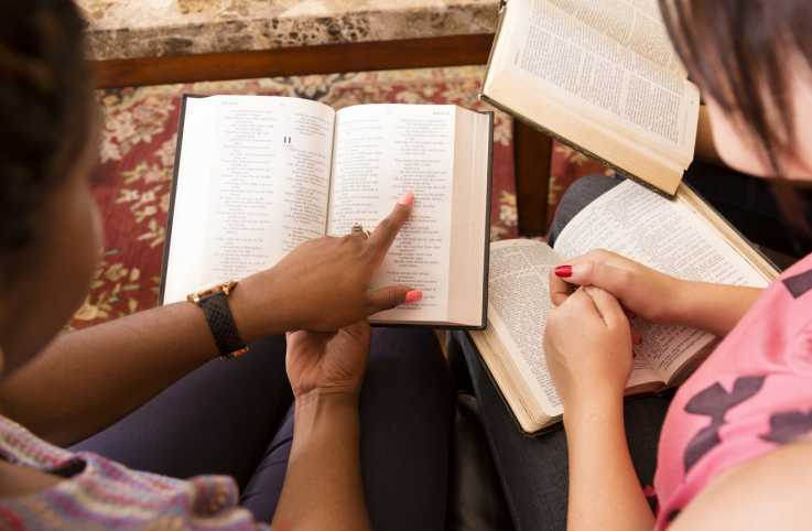 Two women reading the Bible at a Bible study group gathering.