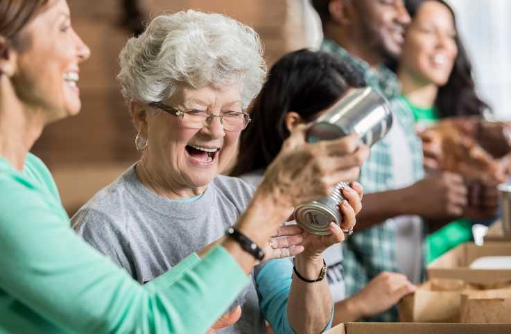 A senior volunteer works at a food bank