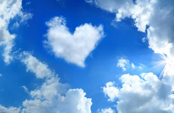 Heart shaped cloud over cloudy and sunny sky with sunbeam