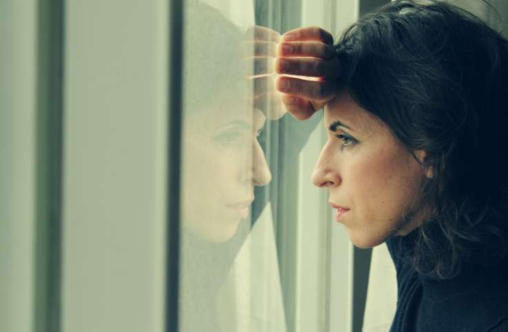 A troubled woman gazes through a window