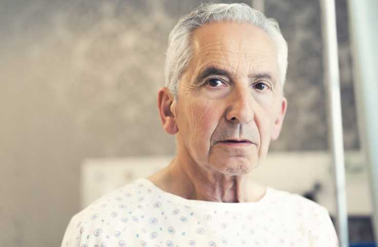 A headshot of a man in a hospital gown.