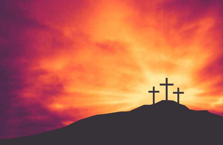 Three Christian Easter and Good Friday Holiday Crosses on Hill of Calvary with Colorful Clouds in Sky Background