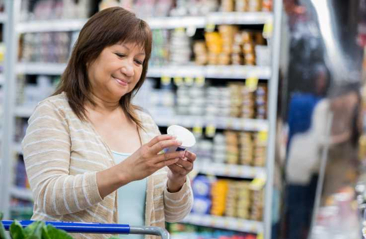 A woman reading a food label in the grocery store.