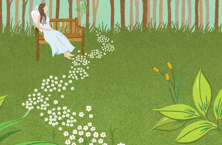 A trail of small, white flowers lead to an angel sitting on a bench in a garden.