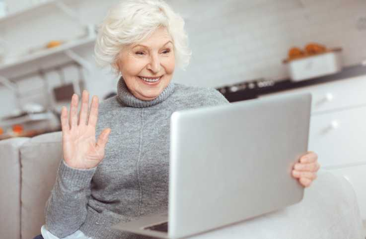 A woman in her golden years using a laptop to video chat.