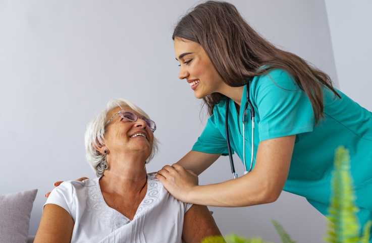 A home care aide helps a patient.