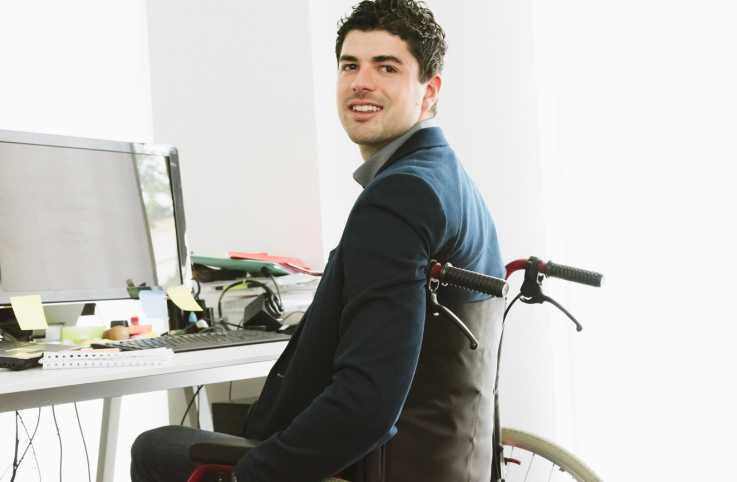 Young handicapped student sitting in wheelchair at his office desk in front of notebook, computer and monitor, looking over with a smile. Natural office interior light.