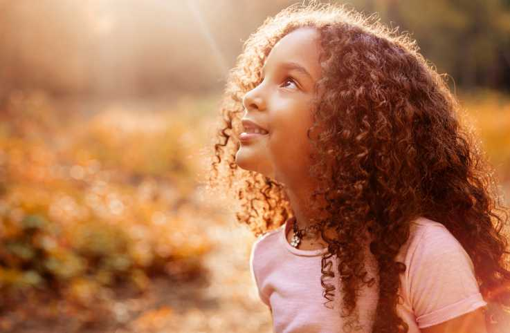 A little girl looking up into the sunlight on a warm, Autumn day.