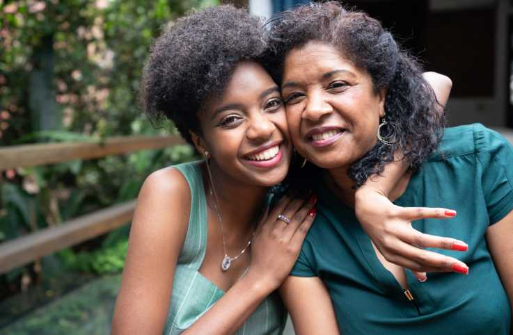 A portrait of a mother and daughter embracing each other.