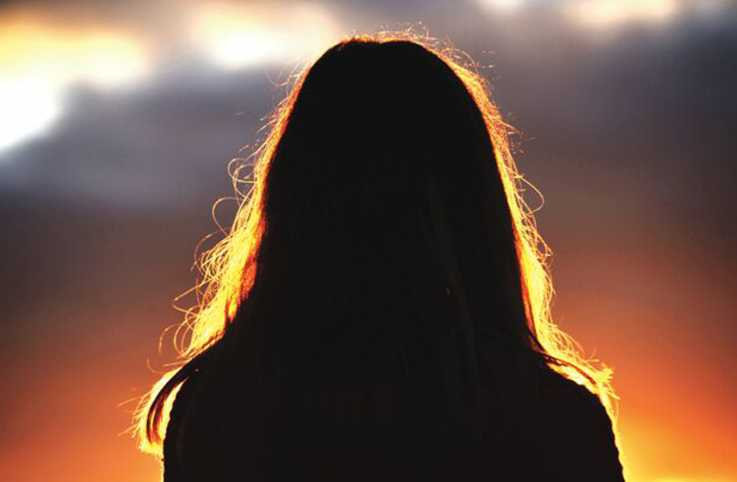 A silouette of the back of a woman's head in mystical light.